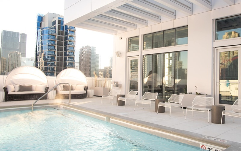 rooftop swimming pool surrounded by plush lounge seating