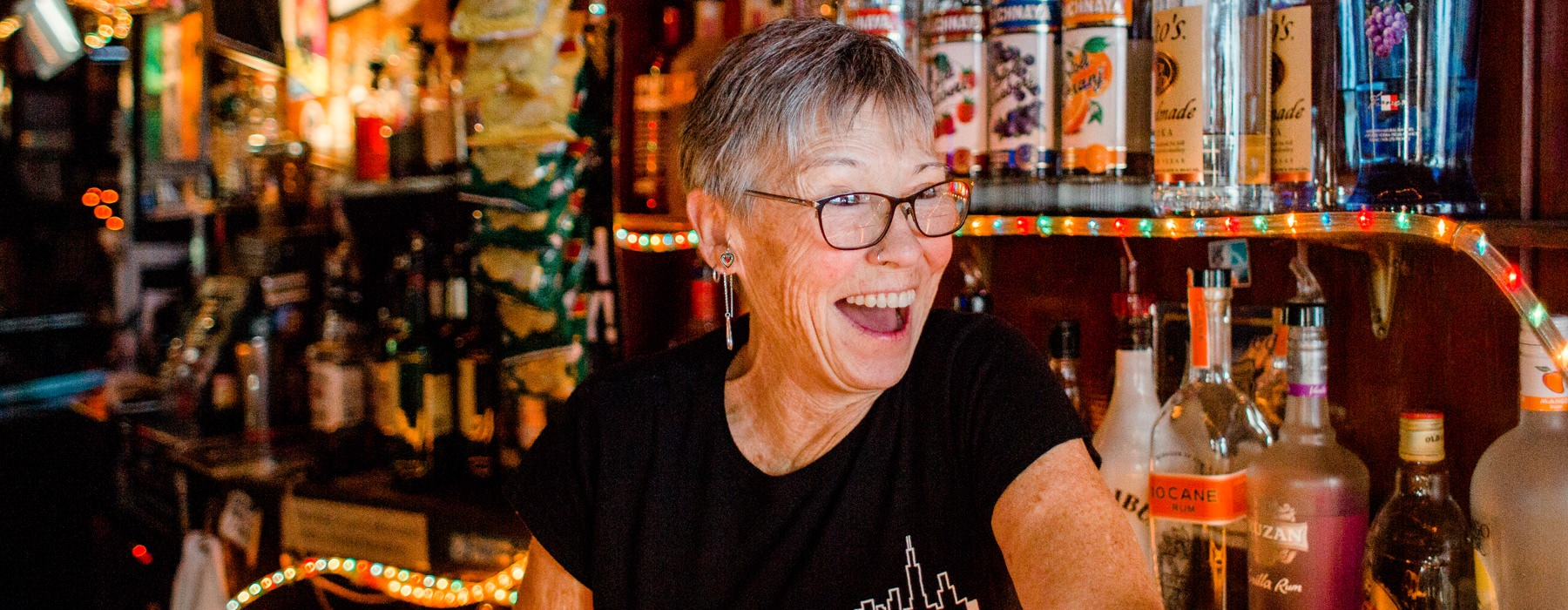 bartender smiling at customers from behind the bar