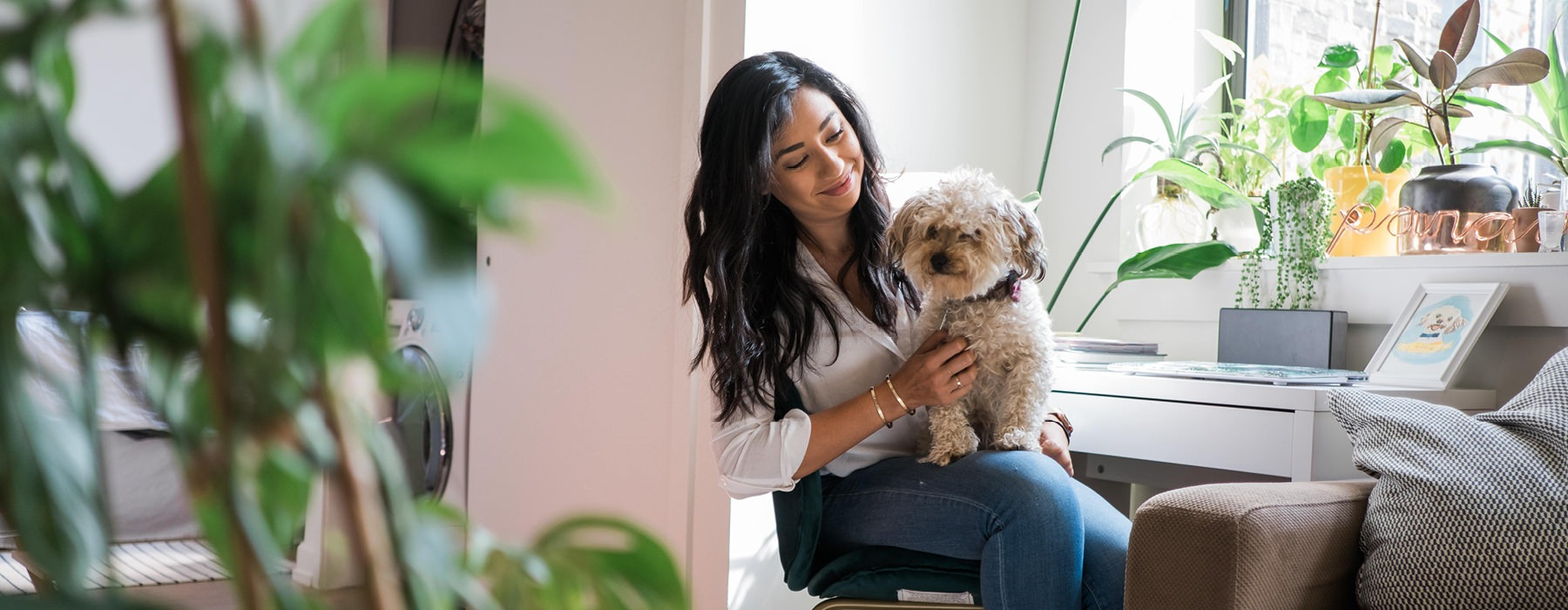 woman at her apartment work area smiling at dog sitting in her lap